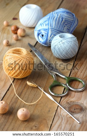 Crochet needles with hook, scissors and wooden beads - stock photo