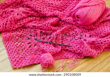 Crochet patterns on the wooden table. Crochet of pink yarn. - stock photo