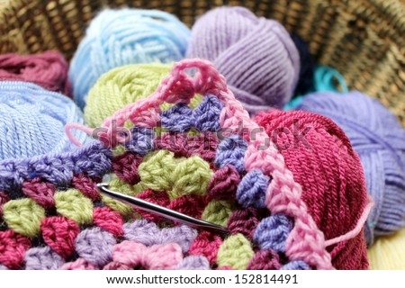 Crochet, the making of a crocheted wool afghan blanket, a retro craft. In a basket with balls of yarn, colors are green, pink, blue and purple - stock photo
