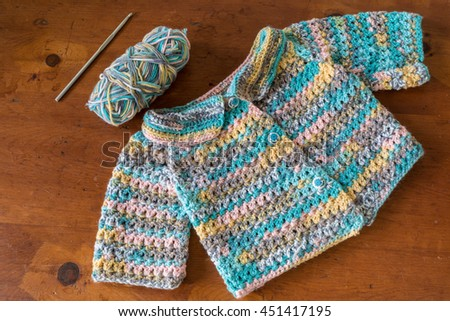 Crocheted baby sweater with a crochet hook and skein of yarn. - stock photo