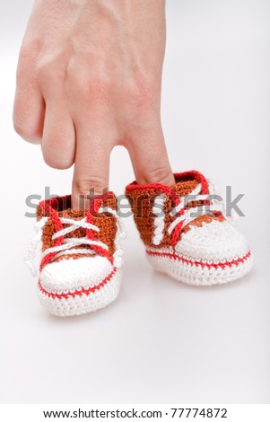 crocheted booties for a boy in the girl's hand - stock photo