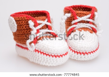 crocheted booties for a boy on a gray background - stock photo
