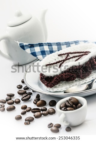 crocheted chocolate cotton cake on plate with ceramic cup of coffee and a small pot - stock photo