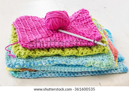 Crocheted dishcloths, with a hook and a ball of yarn. - stock photo