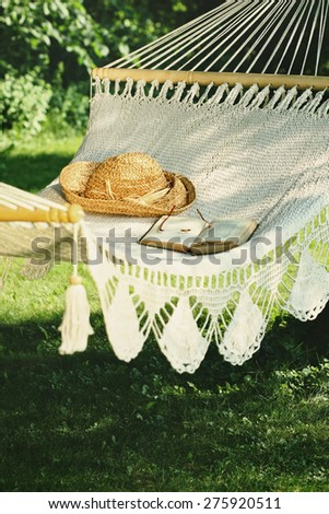 Crocheted hammock with straw hat and book - stock photo