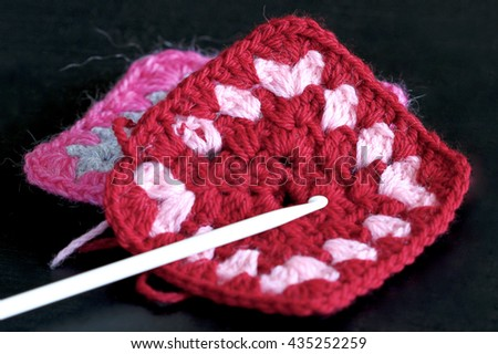 Crocheted knitted squares in red and white.