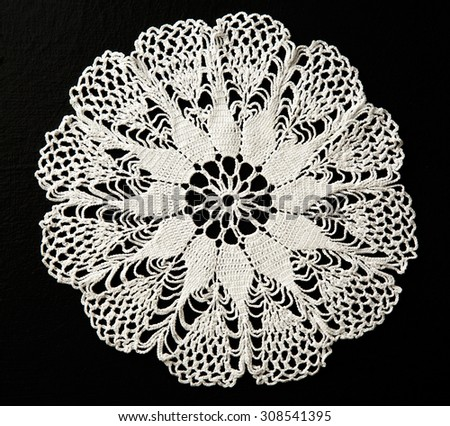 Crocheted white lace decorative napkin on black - stock photo