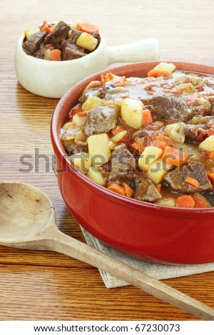 Crock pot full of fresh made roast beef with large chunks of beef, potatoes and carrots. - stock photo