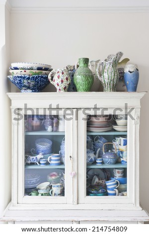 Crockery displayed in storage cabinet at home - stock photo
