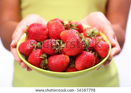 Crockery with strawberries in woman hands. - stock photo
