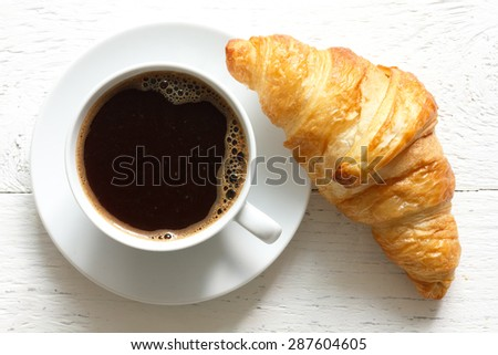 Croissant and coffee on rustic white wood, from above. - stock photo
