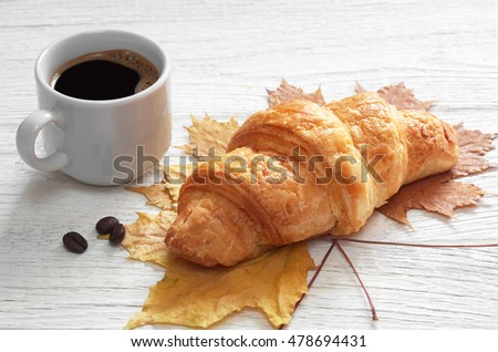 Croissant and cup of hot coffee on white wooden table with autumn leaves