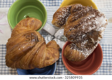 croissant at the honey and at the molten chocolate on some cappuccino cups