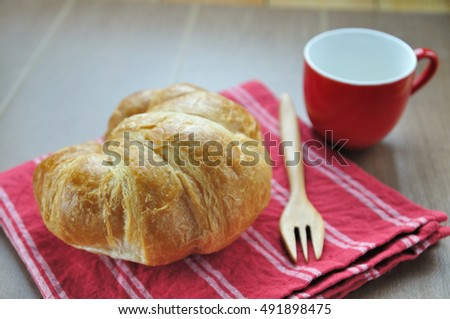 Croissant bread on red napkin with wooden fork and cup of coffee