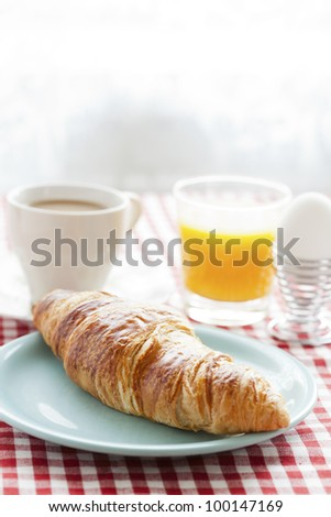 Croissant, cafe au lait, orange juice and an egg for healthy breakfast