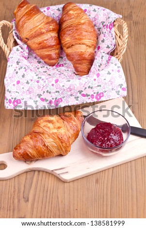 Croissant on a cutting board with jam on a wooden background