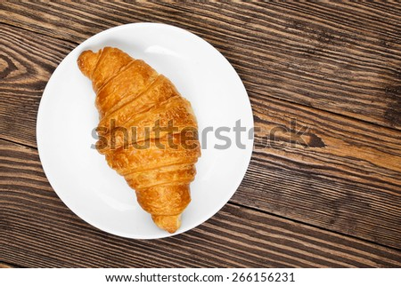 Croissant on a plate standing on an old wooden table. - stock photo