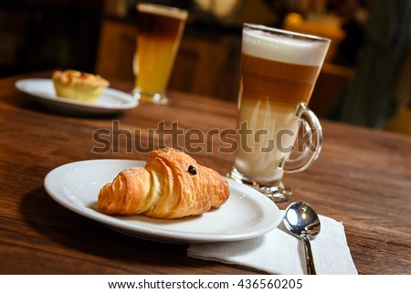 Croissant on plate with coffee on background on brown wood table - stock photo