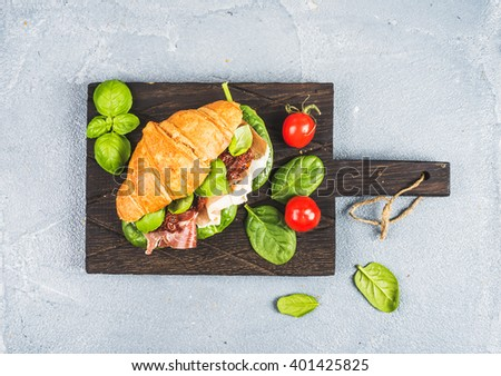 Croissant sandwich with smoked meat Prosciutto di Parma, sun dried tomatoes, fresh spinach and basil on dark wooden board over stone textured grey background, top view - stock photo