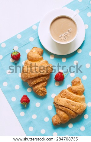 Croissant traditional viennoiserie pastry dessert with a cup of coffe and fresh strawberry on provence style background. Natural light, vivid colors and rustic style. - stock photo