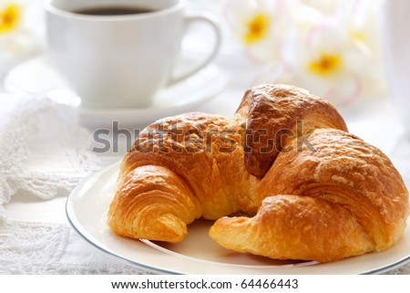 Croissant with coffee, on sunlit breakfast table with lace napkins.