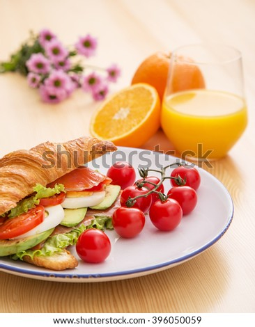 Croissant with fish, tomatoes and lettuce