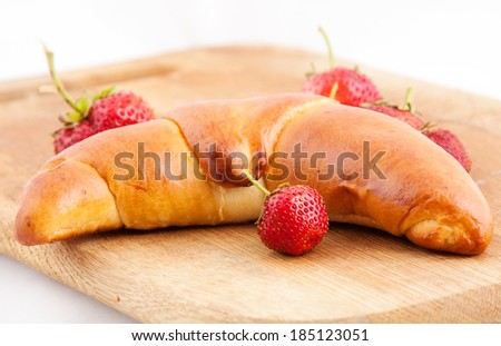 croissant with fresh strawberry on a kitchen board - stock photo