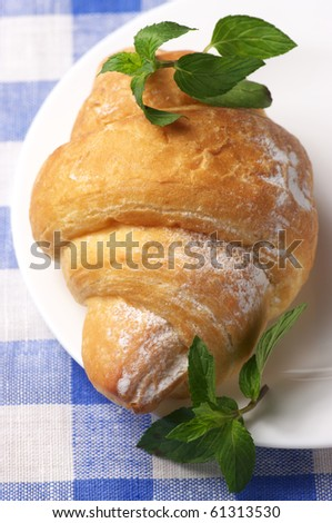 Croissant with mint in white plate on blue checkered tablecloth. - stock photo
