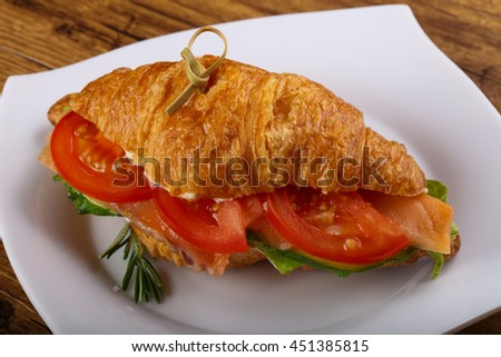 Croissant with salmon served rosemary on wood background