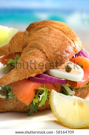 Croissant with salmon, vegetables, egg, lemon, capers on the beach,closeup - stock photo