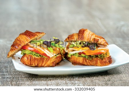 Croissant with smoked turkey, pesto and roasted zucchini and bell pepper. - stock photo