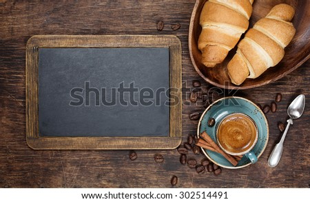 Croissants and coffee  with vintage blackboard with copyspace - stock photo