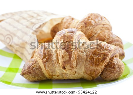croissants in paper pack on plate isolated. horizontal shot - stock photo