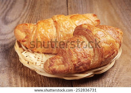 Croissants in wicker wooden plate on rustic wooden table