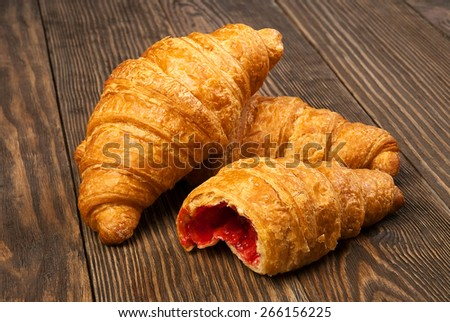 Croissants lying on an old wooden table - stock photo