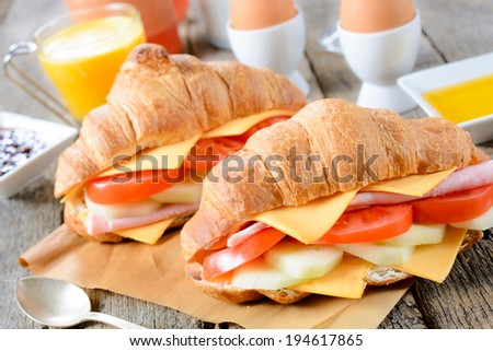 Croissants sandwiches on the wooden table.Selective focus on the front croissant sandwich  - stock photo
