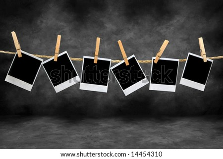 Crooked Old instant photo Film Blanks Hanging on a Rope Held By Clothespins on a Grunge Darkroom Background - stock photo