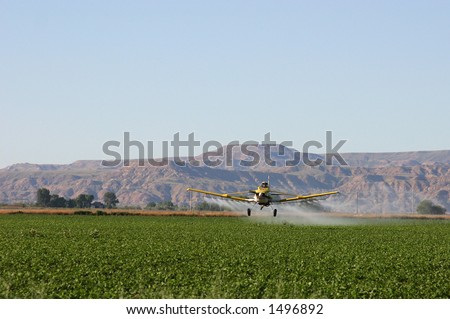 Crop duster dusting field in Wyoming valley - stock photo