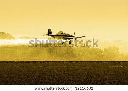 Crop Duster Flying Low over Fields In Late Afternoon - stock photo