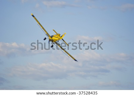 Crop-duster making a turn to come back for another run at the cornfield. - stock photo
