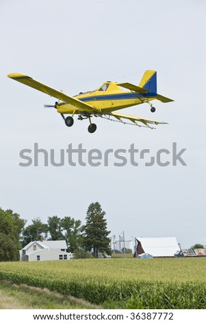 Crop duster over field of corn - stock photo