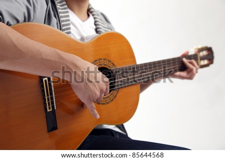 crop image of the man holding a guitar - stock photo