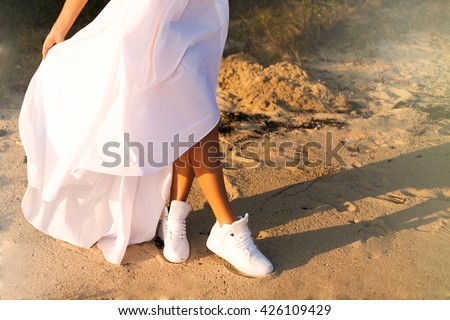 Crop image of young teen women wear white sneakers and long white dress and walking on beach,women with perfect white long dress posing on palm beach,sunset,outdoor image,summer fun.cool teen shoes  - stock photo