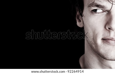 crop of young man's face looking at empty space - stock photo