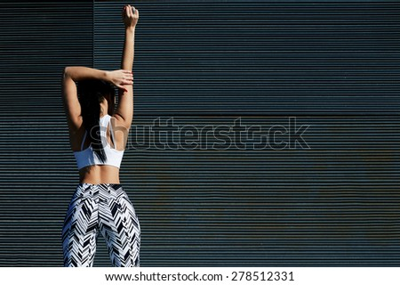 Cropped back view portrait of sporty woman with perfect figure and buttocks stretching her arms against wall with copy space for your text message, fit female exercising on black background outdoors - stock photo