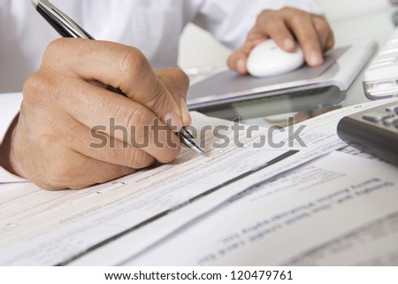 Cropped businessman filling document while using computer at office