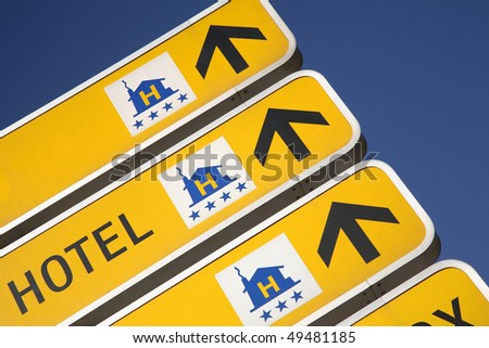 Cropped close-up of a group of yellow signs with arrows showing the way to hotels. Horizontal shot.