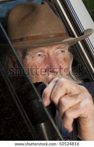 Cropped close-up of an elderly man with a cowboy hat and white beard, driving a pickup truck and staring out the window. Vertical format. - stock photo