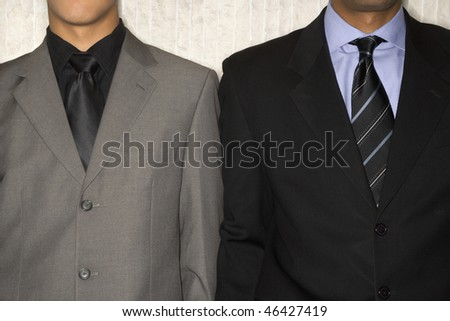 Cropped close-up of the suit jackets and neckties of two businessmen. Horizontal format. - stock photo
