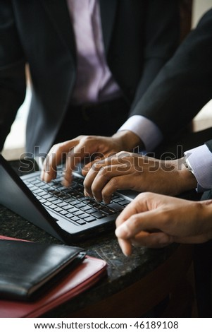 Cropped close-up of three business people and a laptop with the focus on hands typing in the foreground. Vertical format. - stock photo